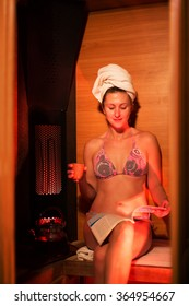 girl in an infrared sauna is drinking tea and reading a magazine.