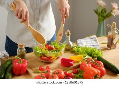Girl interferes with vegetable salad. Cooking salad