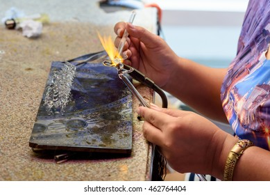 Girl Into shape tiny crystal  by heating that handmade  beautiful jewelry.Shoot on July28, 2016 Suphanburi, Thailand.