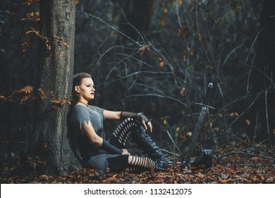 A girl in iron armor. A woman with a sword. The cosplay of a knight. Warrior in the dark forest