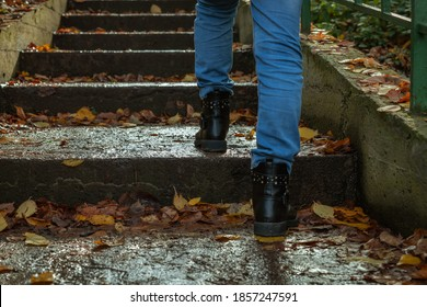 A girl in jeans and boots walks up the wet steps of a staircase covered with fallen autumn leaves in the rain. Selective focus. Copy space for your text. Rainy weather theme.