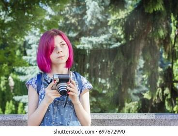 Girl in jeans clothes shooting with instant camera, snapshots outdoor. New generation trends concept. Selective focus