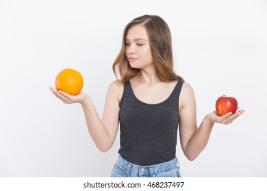 Girl in jeans holds apple and orange and decides which to choose for dessert. Concept of healthy food. Portrait. Isolated