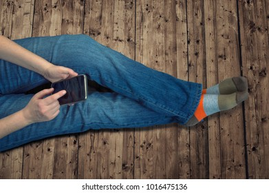 Girl in jeans sitting on the floor at home and using a mobile phone, a top view.