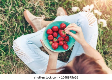 Girl in jeans sitting in summer grass and holding a plate of strawberries, knees and hands visible. Healthy breakfast, Clean eating, vegan food concept. Top view. Toning