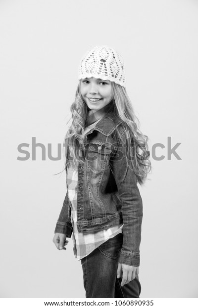 Girl in jeans suit, hat, plaid shirt on orange background. Happy childhood concept. Child smile with long blond hair. Beauty, look, hairstyle. Fashion, style, trend.