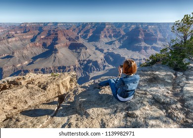 Girl in Jeans Suite is Seating on the Edge of Grand Canyon and Photographing