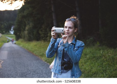 Girl in jeans takes a photo with her smartphone.