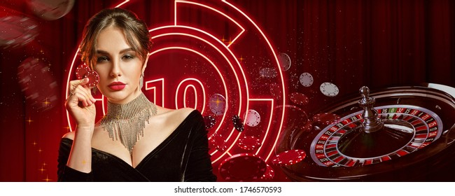 Girl in jewelry and black dress. Showing two red chips, posing on colorful background with neon lights, roulette and chips. Poker, casino. Close-up
