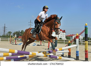 Girl jockey riding a horse jumps over a barrier on equestrian competitions. Girl riding a horse on jumping competitions.