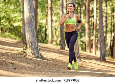 A girl jogging in the woods outdoors.