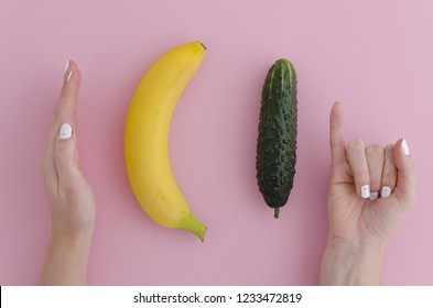 Girl jokingly measures the size of a banana and cucumber comparing with the man dick long or large size. On pink background. Fun photo