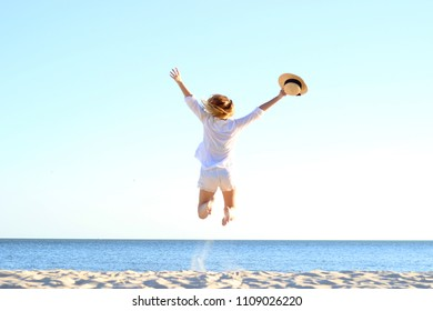 the girl is jumping against the sea.