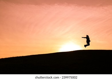 Girl jumping up in the air against a setting sun
