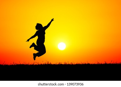 A girl jumping up in the air on top of a hill in front of a blood red sunset.