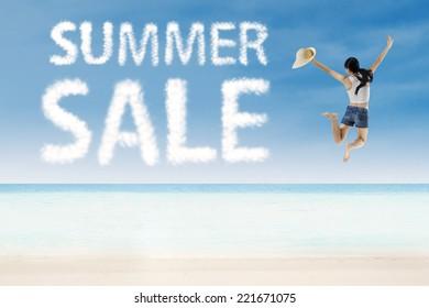 Girl jumping beside summer sale cloud on white sand