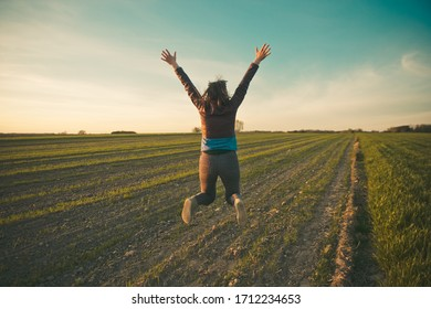 A girl is jumping with hands up with a grat joy and happiness on a field in a countryside under the blue sky and on a green early crop.