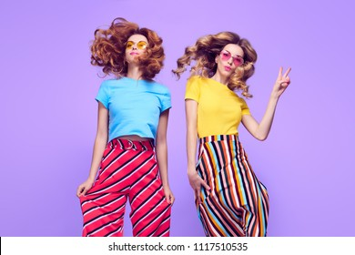 Girl Jumping Having Fun. Young Beautiful Model Woman with Kiss Face Expression in Striped Fashion Trendy Outfit. Playful Blond Redhead Sisters in Studio on Purple