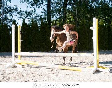 Girl jumping with her pony across hurdle