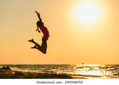 The girl is jumping for joy on the seashore. A stitch on the background of a beautiful sunset.