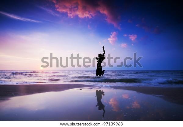Girl jumping for joy on the sunset beach