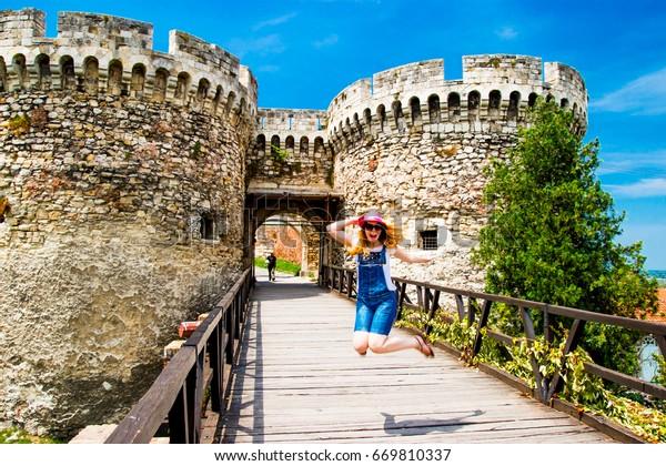 Girl jumping near Belgrade Serbia Old Castle Entrance