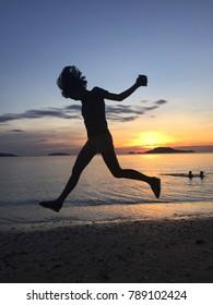 A girl jumping on the beach