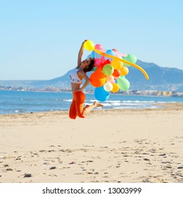 girl jumping on the beach with colorful balloons