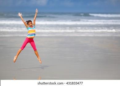 Girl jumping on the beach, Rio de Janeiro, Brazil