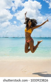 Girl jumping on the beach at Saint-Anne, Martinique, the 25th of February 2018