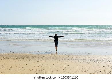Girl jumping on the shore, Atlantic Ocean. Brittany, France