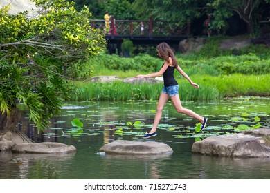 Girl jumping on stones in the lake. Yanoda National Park, Hainan, China.