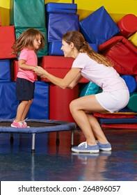 Girl jumping on trampoline with nursery teacher during children sports