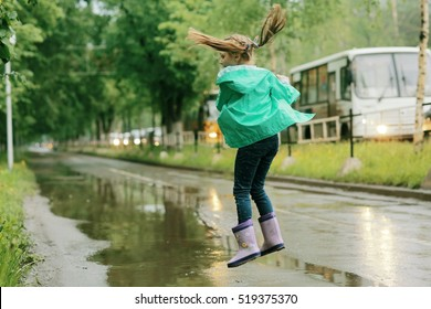 girl jumping in puddles spring rain