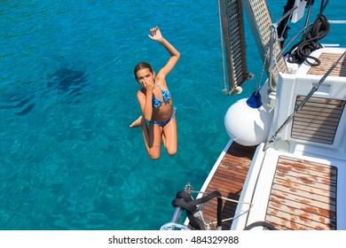 Girl jumping from the sailboat in the clear tropical sea