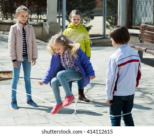 Girl jumping with skipping rope among friends outdoor