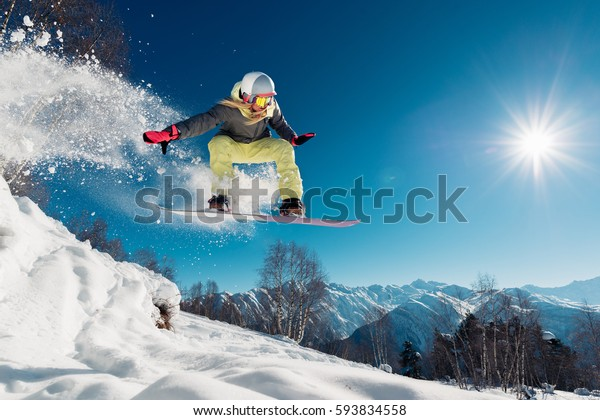 Girl is jumping with snowboard from the hill