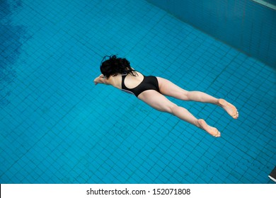 Girl jumping from a spring board at public swimming pool