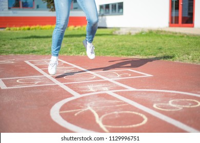 Girl jumping while playing Hopscotch at park. Close-up of little cute girls on children playground outdoors. Legs of kids jumps hopscotch on asphalt.