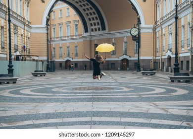 A girl is jumping with an yellow umbrella