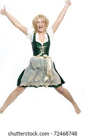 Girl jumps into the air in the dirndl