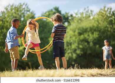 Girl jumps thourgh hula hoop at the park