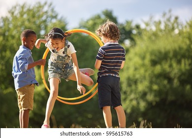 Girl jumps thourgh hula hoop while her friends hold it