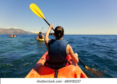 Girl is kayaking on the adriatic sea