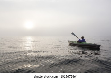 Girl kayaking on an inflatable kayak in Howe Sound during a fog covered winter sunset. Taken in West Vancouver, BC, Canada.