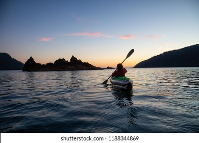 Girl kayaking in the Pacific Ocean during a cloudy summer sunset. Taken in San Josef Bay, Cape Scott, Northern Vancouver Island, BC, Canada.