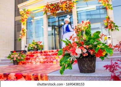 A girl in a Kazakh traditional folk costume stands at the entrance to a building decorated with an autumn design. Clothing of the Kazakh people. National color. Shymkent, Kazakhstan October 14, 2019