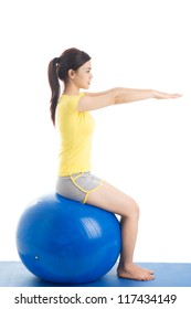 Girl keeping balance sitting on exercise ball, isolated against white background