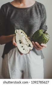 the girl keeps a Soursop fruit or graviola. A young woman holds an guyabano in her hands on a grey background