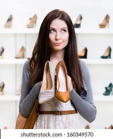 Girl keeps two shoes in the shopping mall and can't choose the one for her